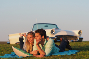 Couple Lying On Blanket In Countryside Next To Classic Carの写真素材 [FYI02126051]