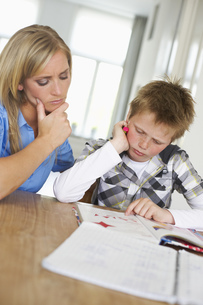 Mother and son concentrating on homework togetherの写真素材 [FYI02126079]