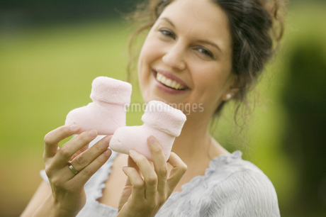 Woman holding up two baby bootsの写真素材 [FYI02126091]