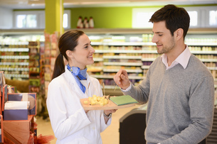 Sales assistant offering customer cheese in an organic grocery storeの写真素材 [FYI02126124]