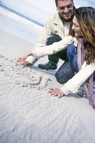 Tilted view of couple writing in the sandの写真素材 [FYI02126137]