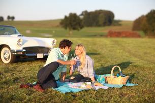 Couple Enjoying Countryside Picnic Next To Classic Carの写真素材 [FYI02126163]