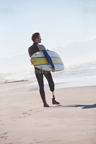 Surfer With Artificial Leg Standing On Beachの写真素材 [FYI02126165]