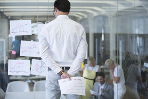 Businessman Studying Documents Stuck To Glass Office Wallの写真素材 [FYI02126166]