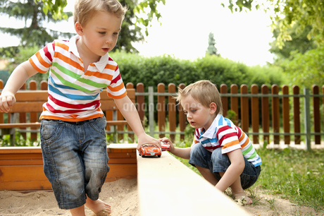 Twin brothers playing in sandpit with toy carsの写真素材 [FYI02126183]