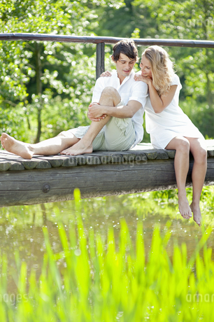 Young couple sitting and relaxing on sunlit footbridgeの写真素材 [FYI02126192]