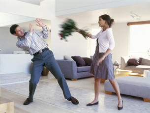 View of woman attacking boyfriend with flowersの写真素材 [FYI02126215]