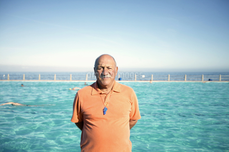 Portrait of an older man standing in front of a pool against blue skyの写真素材 [FYI02126236]
