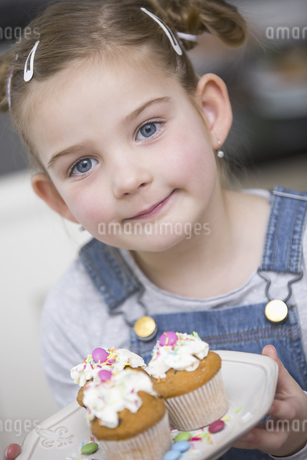 Portrait of young girl holding cupcakesの写真素材 [FYI02126239]