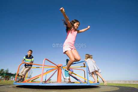 Children jumping off merry-go-round at playgroundの写真素材 [FYI02126240]