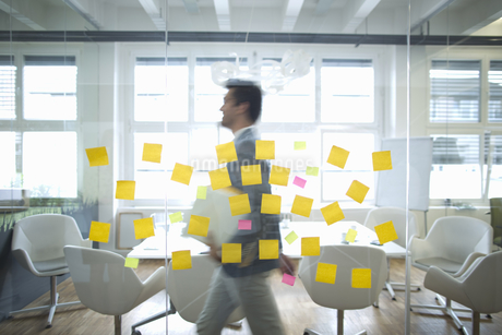 Businessman Walks Past Glass Wall Covered In Sticky Notesの写真素材 [FYI02126241]