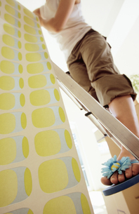 Low angle view of a young woman hanging wallpaperの写真素材 [FYI02126249]