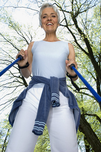 Low angle view of senior woman with walking sticks outdoorsの写真素材 [FYI02126271]