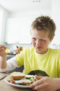 Young boy looking disgusted at vegetablesの写真素材 [FYI02126273]