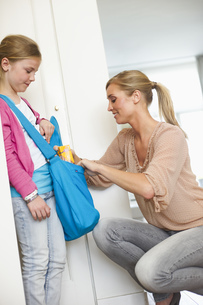 Mother putting drink in daughter's bag for schoolの写真素材 [FYI02126290]