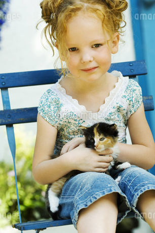 Young girl sitting in chair with kitten outdoorsの写真素材 [FYI02126323]