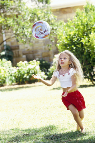 Young girl chasing ball, outdoorsの写真素材 [FYI02126347]