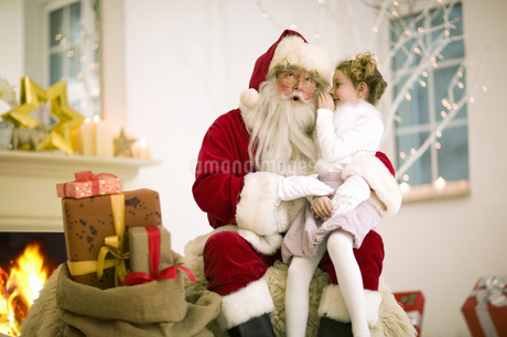 Young girl whispering in Santa Clause ear on Christmasの写真素材 [FYI02126369]