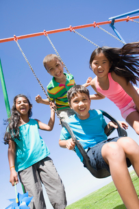 Children smiling together at swing set on playgroundの写真素材 [FYI02126392]