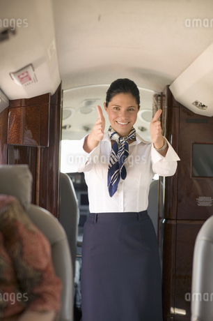 Female flight attendant giving safety demonstration on airplaneの写真素材 [FYI02126448]