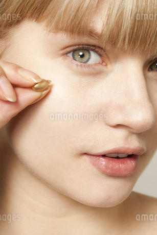 Portrait of young woman applying make upの写真素材 [FYI02126479]