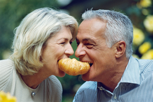 Mature couple playfully sharing a croissantの写真素材 [FYI02126487]