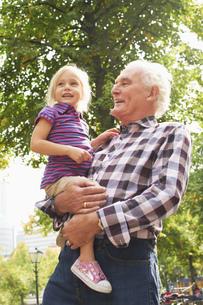 Senior man carrying granddaughter in parkの写真素材 [FYI02126488]