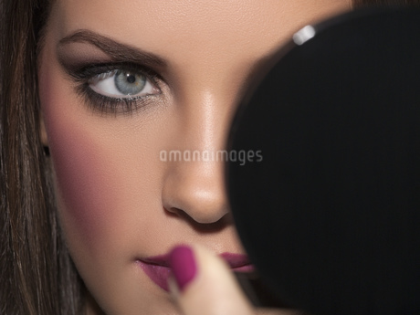 Close-up of young woman looking in compact mirrorの写真素材 [FYI02126523]
