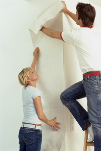Portrait of a young couple putting up wallpaperの写真素材 [FYI02126575]