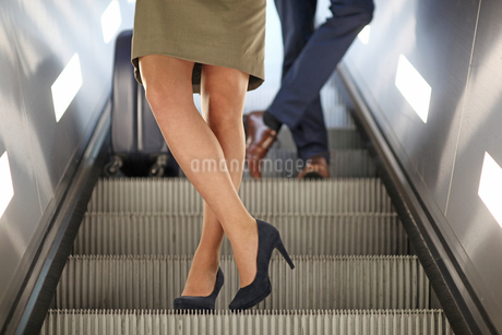 Businesswoman in high heels travelling on escalator, Munich, Bavaria, Germany, Europeの写真素材 [FYI02126582]