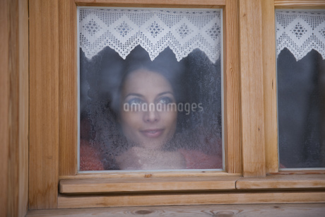 Mid adult woman looking though windowの写真素材 [FYI02126613]