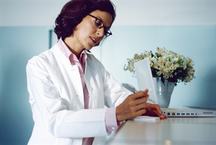 Portrait of a young female doctor signing a formの写真素材 [FYI02126619]