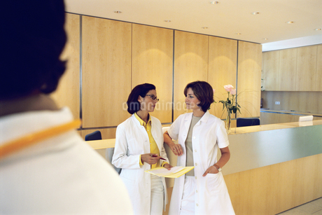 View of two young female doctors talking in office settingの写真素材 [FYI02126626]