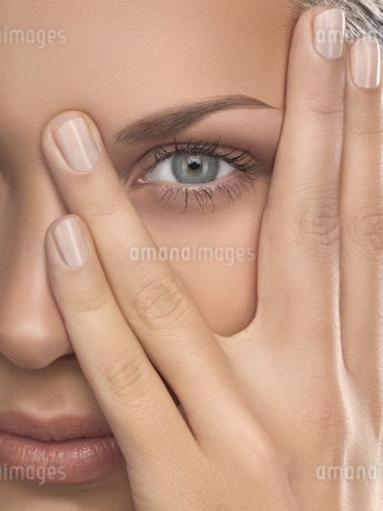 Close-up of young woman with hand on face, studio shotの写真素材 [FYI02126664]