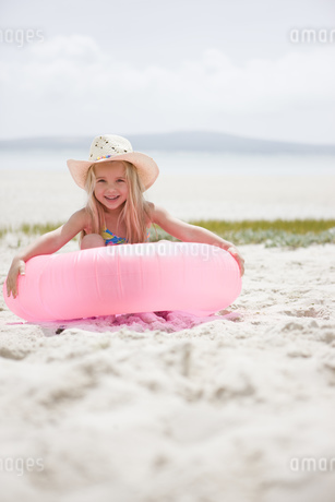 Portrait of young girl smiling with pink inflatable on beachの写真素材 [FYI02126669]