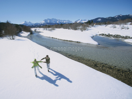 High angle view of a young couple playing in snow in winter setting, Isar, Bavaria, Germanyの写真素材 [FYI02126672]
