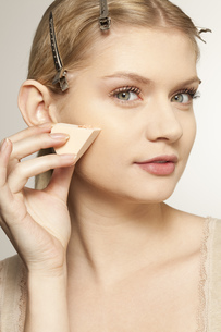 Portrait of young woman using skin care productの写真素材 [FYI02126677]