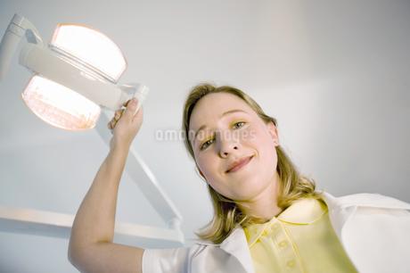 Female dental assistant smiling and adjusting dental lightの写真素材 [FYI02126682]
