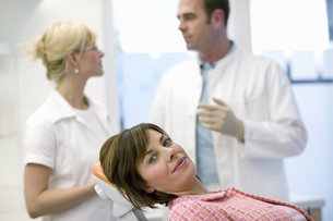 Patient in dentists chair with dentist in backgroundの写真素材 [FYI02126687]