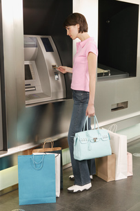 Female shopper using an automated banking machineの写真素材 [FYI02126700]