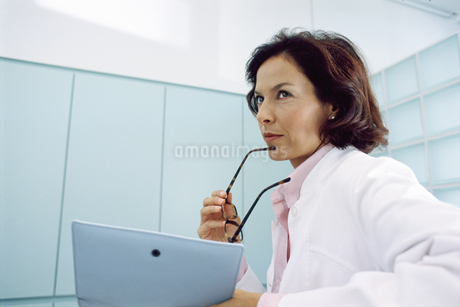 Low angle view of a female doctor looking at a clipboardの写真素材 [FYI02126734]