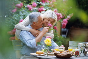 Mature couple embracing and having breakfast outdoors, with selective focusの写真素材 [FYI02126742]