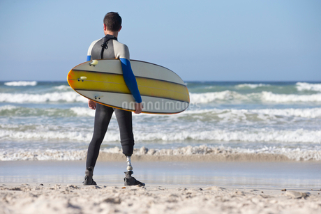 Surfer With Artificial Leg Standing On Beachの写真素材 [FYI02126759]