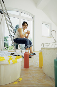 Portrait of a young woman sitting on a ladder having a cup of coffee in her unfinished living roomの写真素材 [FYI02126791]
