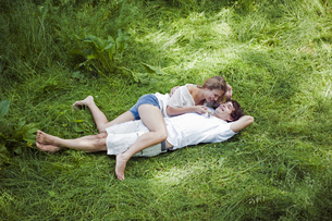 Young couple lying together in long grassの写真素材 [FYI02126802]