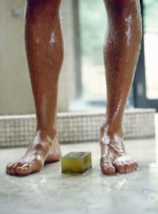 View of a young man's legs in the shower with a bar of soap between his feetの写真素材 [FYI02126803]