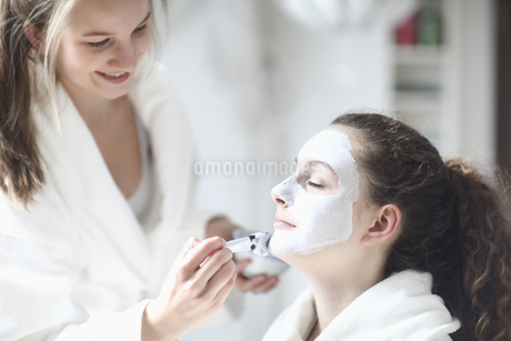 Teenage girl applying face mask to friendの写真素材 [FYI02126827]