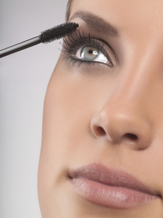 Close-up portrait of young woman applying mascara, studio shotの写真素材 [FYI02126828]