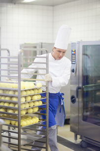Chef with tray of food in kitchenの写真素材 [FYI02126836]