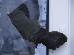Burglar reaching through broken glass on doorの写真素材 [FYI02126852]